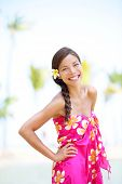 Woman on beach - smiling happy cheerful. Pretty female model in sarong enjoying resort travel vacation holidays in sun. Beautiful mixed race Asian Caucasian girl on Hawaii, United States.