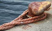 image of bollard  - Old rusted mooring bollard with red naval rope on concrete pier - JPG