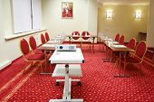 Projector, red chairs and tables in small room with red carpet for business meetings.