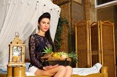 Beautiful woman sits on bed and holds basket with different fruits in bedroom.