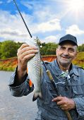 picture of chub  - chub in the hand of fisherman against the sky and the river - JPG