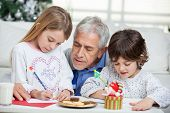Grandfather assisting children in writing letters to Santa Claus during Christmas at home