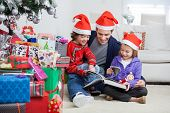 Happy siblings and father in Santa hats reading book while sitting by Christmas presents at home