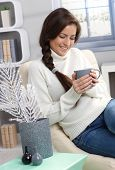 Smiling woman enjoying hot tea at winter, sitting in cosy living room.