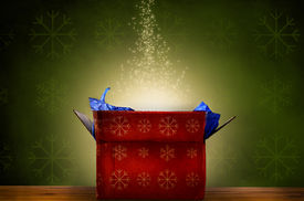 stock photo of tissue box  - An opened red Christmas gift box with gold snowflake patterns emitting a magical warm bright glowing light and rising sparkling stars - JPG