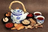 Chinese herb tea selection with traditional teapot and cups over brown lokta handmade paper background.