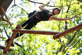 stock photo of daring  - Young caucasian attractive woman climbing in adventure rope park in mountain helmet and safety equipment - JPG