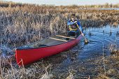 senior male paddling a red canoe through a wetland in early spring