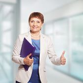 image of 55-60 years old  - attractive woman 50 years old with a folder for documents - JPG