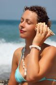 Beautiful Woman Has Leant Seashell Bowl To An Ear On Seacoast