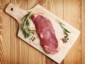 Raw sirloin steak with rosemary and spices on cutting board over wooden table