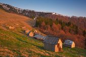 Wooden houses for shepherds and sheep barns in the mountains. Spring landscape with the village of shepherds. Carpathian mountains, Ukraine, Europe