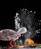 Chicken meat with flour in freeze motion, isolated on black background