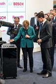 HANOVER, GERMANY - APRIL 7: German Chancellor Angela Merkel during a technology showcase tour of industrial Robotics by Bosch and Rexroth at the Hannover Messe