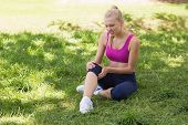 Full length of a healthy and beautiful young woman in sportswear sitting in the park