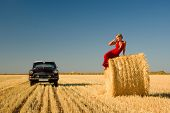 Girl Leaning On Straw Bale With Retro Car Background.