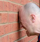 image of slam  - a man banging his head against the wall in frustration
