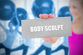Fit blonde holding card saying body sculpt against fitness class in gym