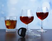 Composition with car key and glasses of drinks, on wooden table, on bright background