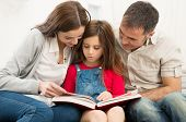 Mother And Father Helping Their Daughter While Reading Book