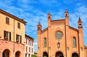 View of city hall building and San Lorenzo (Duomo) cathedral under blue sky with white clouds in town of Alba in Piedmont, Northern Italy.