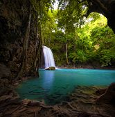 Waterfall in tropical forest. Beautiful nature background. Jungle trees and blue water of mountain r