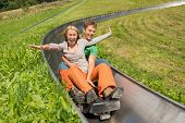 picture of luge  - Excited young couple enjoying alpine coaster luge during summer - JPG