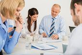 Business team discussing document in boardroom meeting