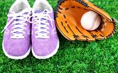 Beautiful gumshoes and baseball ball, glove on green grass, on bright background