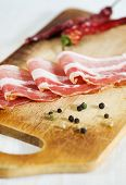 picture of bacon strips  - Slices of bacon and pepper on the chopping board - JPG