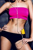 attractive fitness woman in pink top with mp3 player, closeup body shot