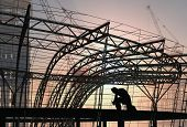 Silhouette of a welder and a building structure.