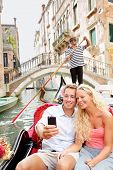 Travel couple in Venice on Gondole ride romance in boat happy together on travel vacation holidays.