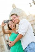 Tourists couple selfie by Vatican city and St. Peter's Basilica church in Rome. Happy travel woman and man taking selfie photo picture on romantic honeymoon in Italy.