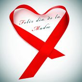 a red satin ribbon forming a heart and the sentence feliz dia de la madre, happy mothers day written