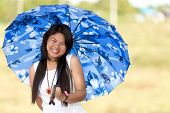 Beautiful young Thai girl under a blue sunshade or umbrella to protect her against the hot summer su