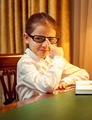 Young Girl In Eyeglasses Sitting Behind Desk