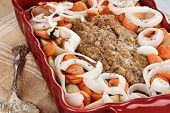 picture of meatloaf  - Casserole dish of freshly prepared meatloaf with onions carrots and potatoes - JPG