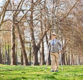 stock photo of crutch  - Senior man walking with crutches outdoors shot with tilt and shift lens - JPG