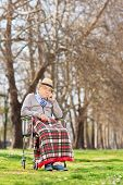 Displeased senior sitting in a wheelchair outdoors