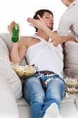 image of couch potato  - Woman slapping her couch potato husband vertical - JPG