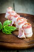 foto of bacon strips  - Rolled Bacon Strips On Wooden Board Close Up - JPG