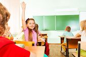 Girl holds hand up by turned back in classroom