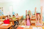 Happy children with arms up sitting in classroom