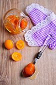 stock photo of kumquat  - Jam from the whole kumquats lies in the spoon against the background of the glass jar - JPG