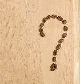 Coffee Beans Are Laid Out On A Wooden Board In The Form Of A Question Mark