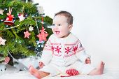 Funny Laughing Baby Girl Playing Under Red And White Decorated Christmas Tree Wearing Knitted Jacket