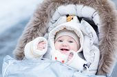 Laughing Baby Girl Enjoying Walk In A Snowy Winter Park Sitting In Stroller With sheepskin hood