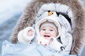 Laughing Baby Girl Enjoying Walk In A Snowy Winter Park Sitting In Stroller With sheepskin hood