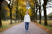 Happy Laughing Boy Walking Down A Beautiful Road Between Colorful Yellow Autumn Trees
